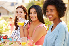 3 женских друз наслаждаясь едой на внешней партии Стоковые Фотографии RF