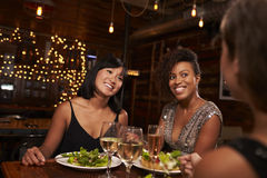 3 женских друз наслаждаясь обедающим на ресторане Стоковое Изображение