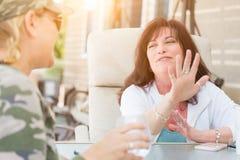 2 женских друз наслаждаясь переговором снаружи Стоковые Фотографии RF