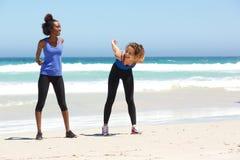 2 женских друз наслаждаясь разминкой на пляже Стоковая Фотография RF