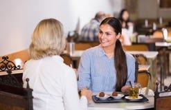 2 женских друз на таблице кафа Стоковые Изображения