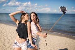 2 женских друз принимая selfie на пляже посылая поцелуи Стоковое фото RF