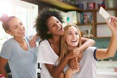 3 женских друз принимая Selfie пока делающ завтрак Стоковое Изображение RF