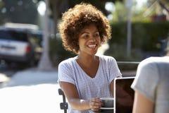 2 женских друз при компьтер-книжка сидя на таблице вне кафа Стоковое фото RF
