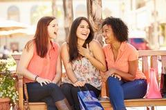 3 женских друз при хозяйственные сумки сидя в моле Стоковое фото RF