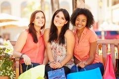 3 женских друз при хозяйственные сумки сидя в моле Стоковые Изображения