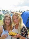 2 женских друз располагаясь лагерем на музыкальном фестивале Стоковые Фотографии RF
