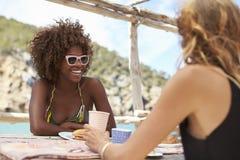 2 женских друз сидят говорить на таблице морем, Ibiza Стоковые Фото