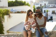 2 женских друз сидя на путеводителе чтения стены, Ibiza Стоковое Фото