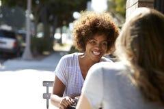 2 женских друз сидя на таблице вне кафа Стоковые Изображения RF