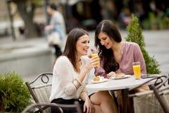 2 женских друз сидя снаружи в кафе Стоковые Изображения RF