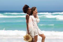 2 женских друз смеясь над на пляже Стоковые Фотографии RF