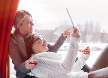 2 женских друз смотря планшет Стоковое Фото