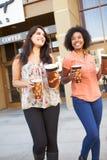 2 женских друз стоя внешнее кино совместно Стоковые Изображения