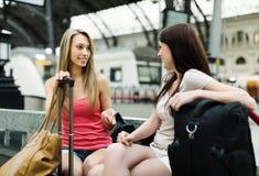 2 женских друз с багажом на железнодорожном вокзале Стоковые Фотографии RF