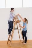 2 женских друз с лестницей в новом доме Стоковое фото RF