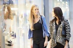 2 женских друз с сумками в торговом центре Стоковая Фотография