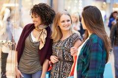 3 женских друз ходя по магазинам в моле совместно Стоковое Изображение RF