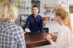 2 женских друз flirting с красивым барменом Стоковые Фотографии RF