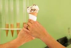 2 женских руки держа ваниль с конусом мороженого шоколада Женщина продает мороженое в магазине печенья Стоковые Фотографии RF
