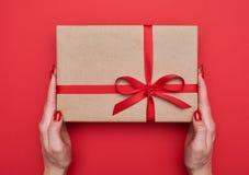 2 женских руки держат славную подарочную коробку связанный с красной лентой Стоковое Фото