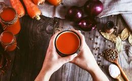 2 женских руки держа железную кружку с соком моркови Стоковая Фотография