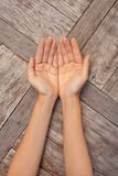 2 женских руки показывая открытые ладони на деревянной предпосылке Стоковая Фотография