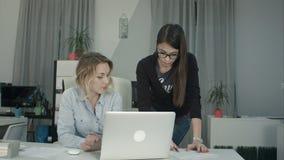 2 женских сотрудника обменивая идеи о отчете смотря компьтер-книжку Стоковые Изображения