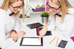 2 женских сотрудника обсуждая проект Стоковые Фотографии RF