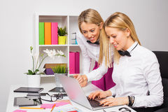 2 женских сотрудника работая в команде на компьтер-книжке Стоковая Фотография RF