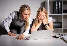 2 женских сотрудника смотря компьютер в неверии Стоковое Изображение RF