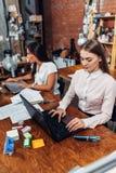 2 женских студента колледжа подготавливая для уроков используя компьтер-книжку сидя на столе в комнате исследования Стоковое Изображение RF