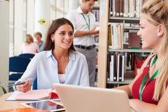 2 женских студента колледжа изучая в библиотеке совместно Стоковые Изображения
