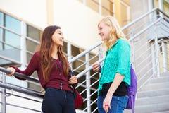 2 женских студента средней школы стоя внешнее здание Стоковое фото RF