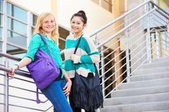 2 женских студента средней школы стоя внешнее здание Стоковая Фотография