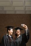 2 женских студент-выпускника принимая фотоснимок Стоковое Фото