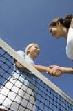 2 женских теннисиста тряся руку над взглядом низкого угла сети теннисного корта Стоковое Изображение RF