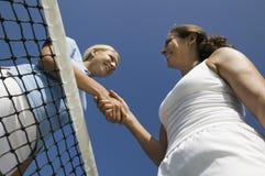 2 женских теннисиста тряся руку над взглядом низкого угла сети теннисного корта Стоковые Изображения RF