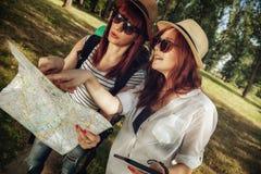 2 женских туриста просматривая карту Стоковая Фотография