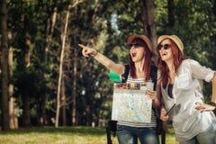 2 женских туриста просматривая карту Стоковое фото RF