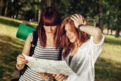 2 женских туриста просматривая карту Стоковые Изображения