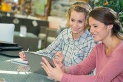 2 женских фрилансера сидя с электронными устройствами Стоковые Изображения