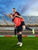 2 женских футболиста празднуя победу на хранят футболе, который стоковое изображение rf