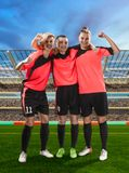 3 женских футболиста празднуя победу на хранят футболе, который стоковое изображение