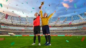 2 женских футболиста держа чашку победы на толпить стадионе Стоковая Фотография RF