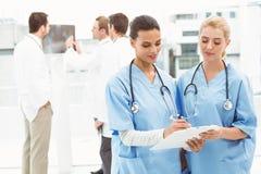 2 женских хирурга смотря отчеты Стоковые Фотографии RF