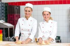 2 женских хлебопека в тесте хлебопекарни замешивая на хлебопекарне Стоковая Фотография RF