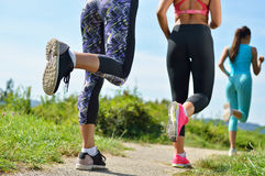 3 женских Joggers бежать совместно outdoors стоковая фотография