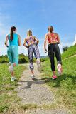 3 женских Joggers бежать совместно outdoors стоковое изображение