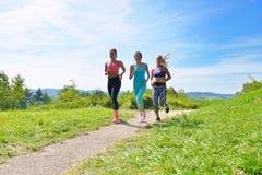 3 женских Joggers бежать совместно outdoors Стоковые Фотографии RF
